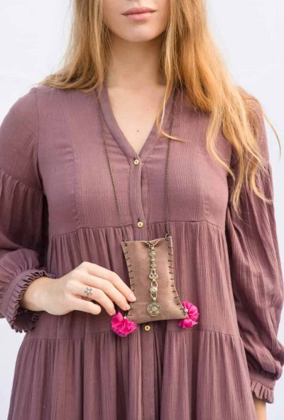 mauve suede purse with pink pompoms and brass coins