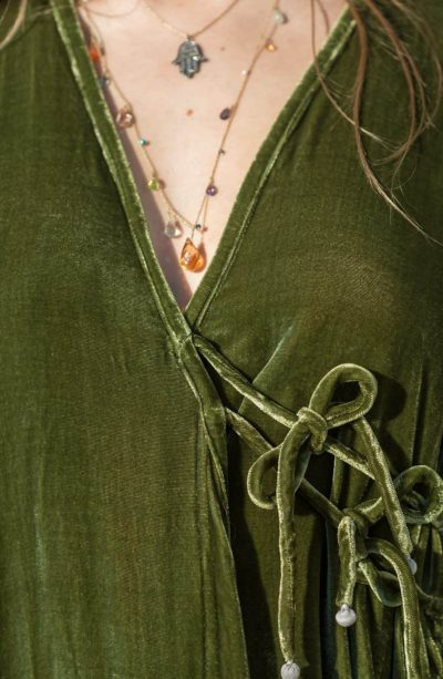 close up of the ties on a green velvet coat