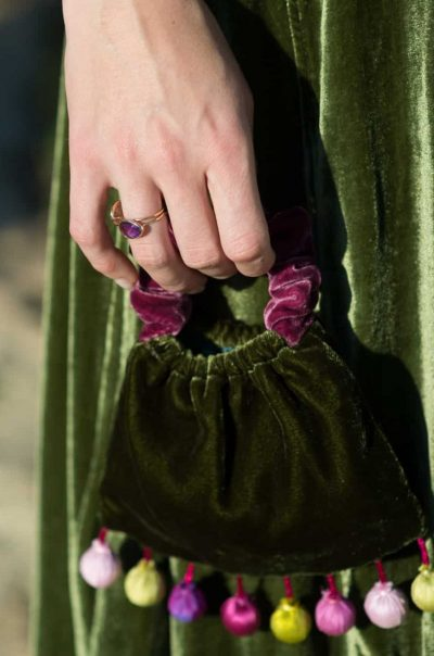 amethyst wire ring worn with a green velvet bag with silk balls