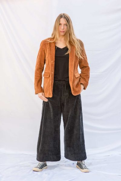 charcoal grey wide leg corduroy trousers worn with rusty orange corduroy jacket with brass buttons