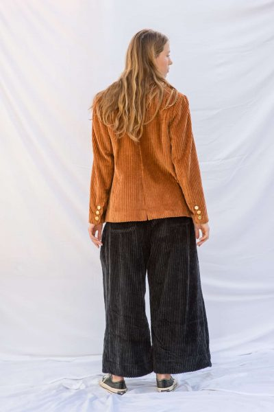 charcoal grey corduroy trousers worn with rusty orange corduroy jacket with brass buttons