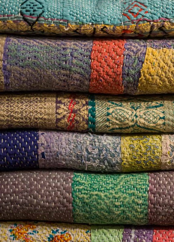 stack of folded blankets with Kantha stitching