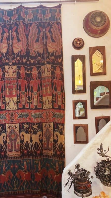 long wall hanging with intricate embroidery displayed next to wooden mirrors