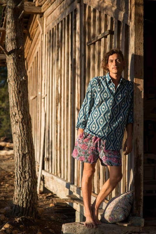 blue shirt in an ikat print worn with pink floral shorts