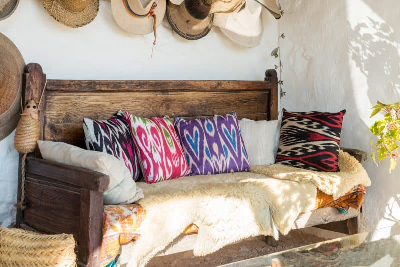 colourfully woven ikat cushions on a wooden bench