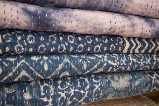 pike of folded blue blankets