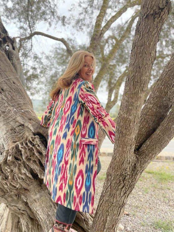 tree climbing wearing a woven ikat coat