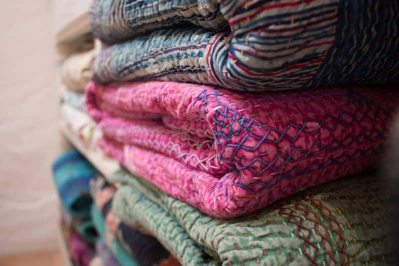 pile of colourful blankets with running kantha stitch