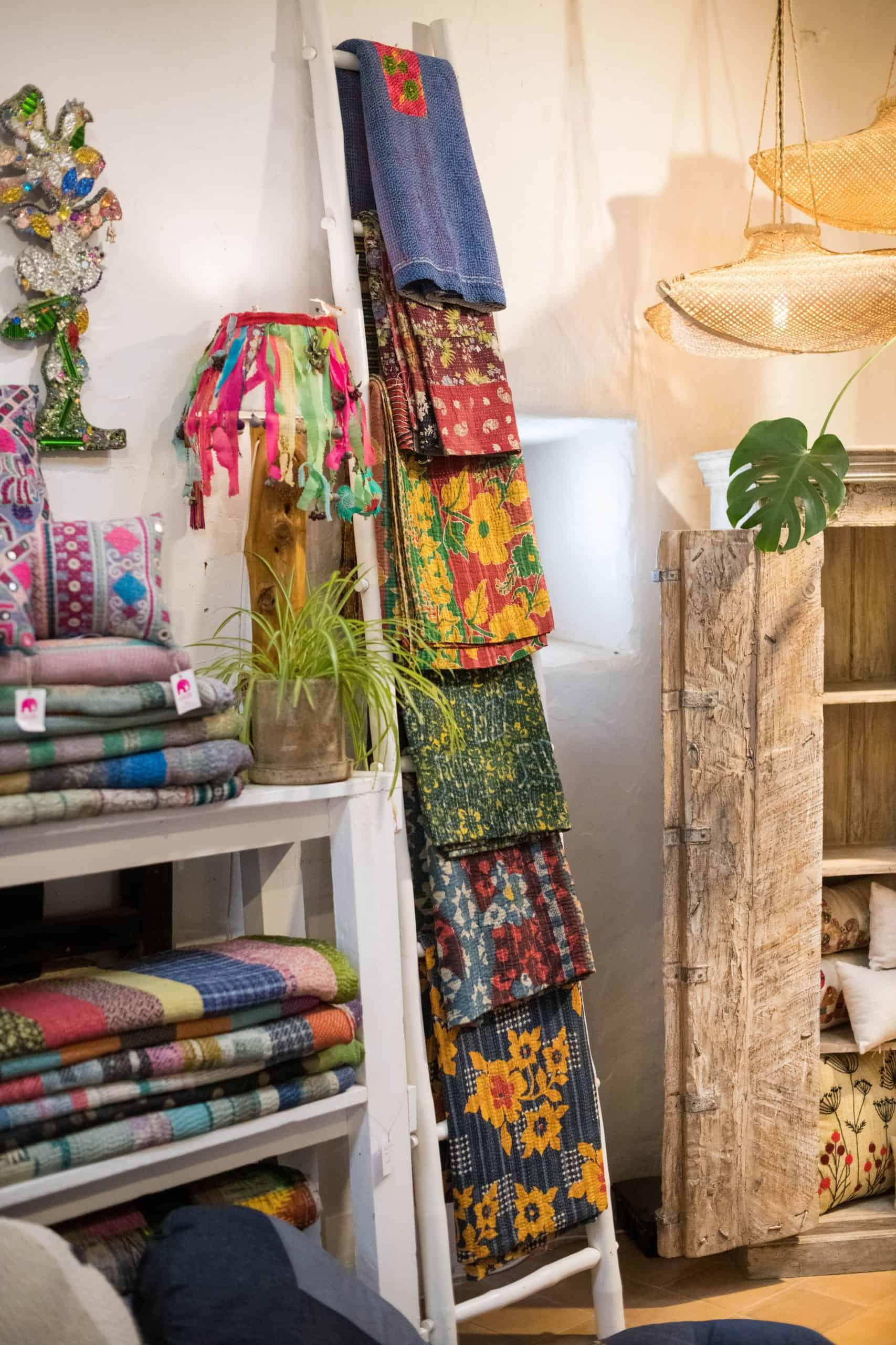 Kantha blankets displayed on a ladder