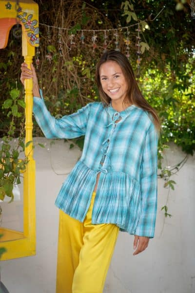 pleated blue jacket worn with silk trousers in yellow