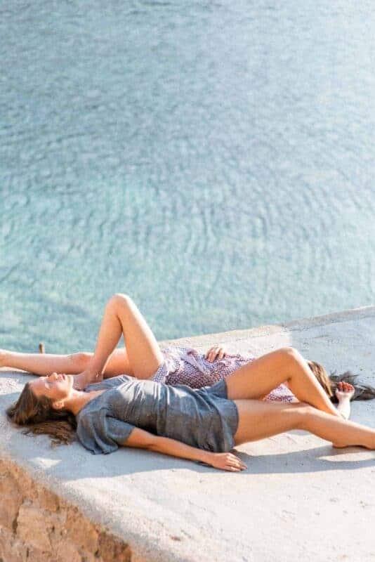 two girls by the sea sunbathing