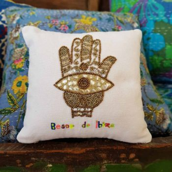 embroidered hamsa hand in gold on a small cushion