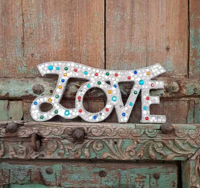 the word love on a glittered sign